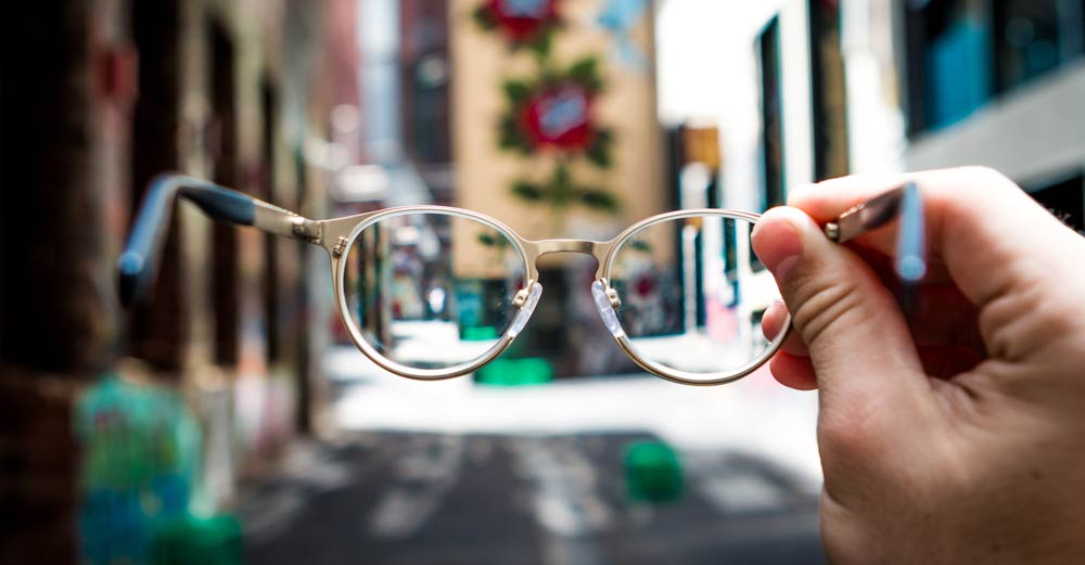 eyeglasses held in hand with city in background