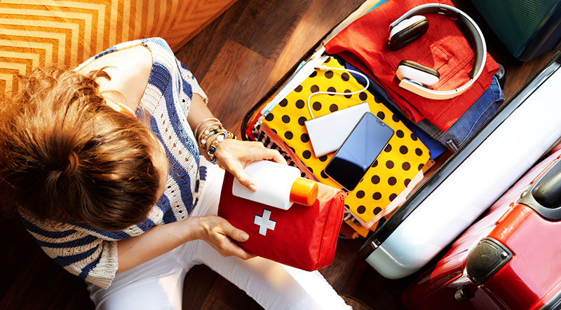 woman packing luggage with travel first aid kit and sunscreen