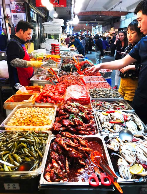 Food market with tourists in Seoul, South Korea.