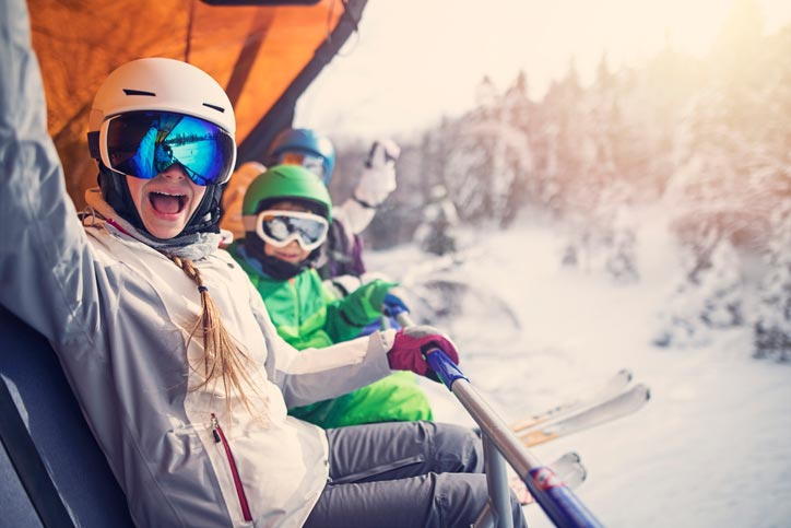 Kids and family on ski lift in snow at one of the best ski resorts in the US