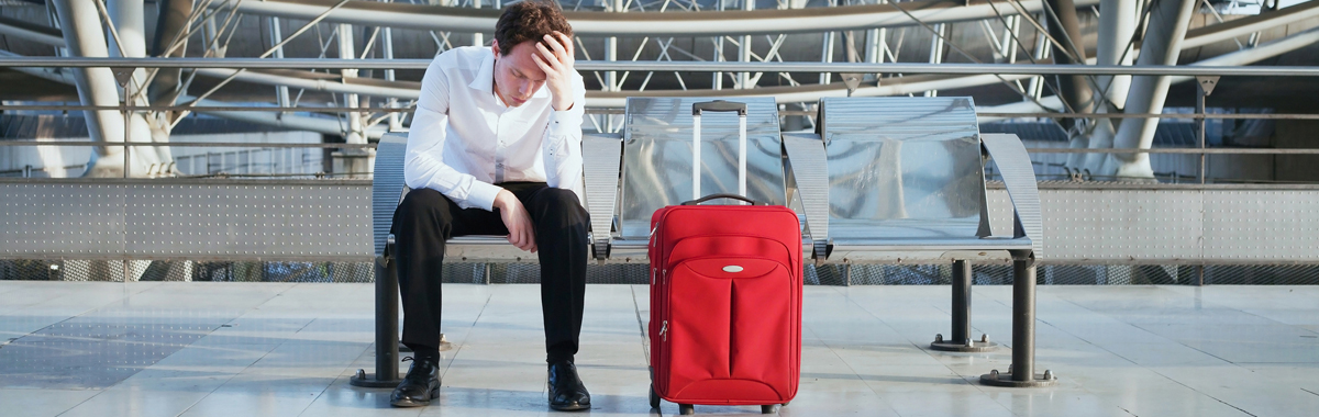 Man in an airport with luggage upset about his canceled flight and that he doesn't have trip cancellation insurance