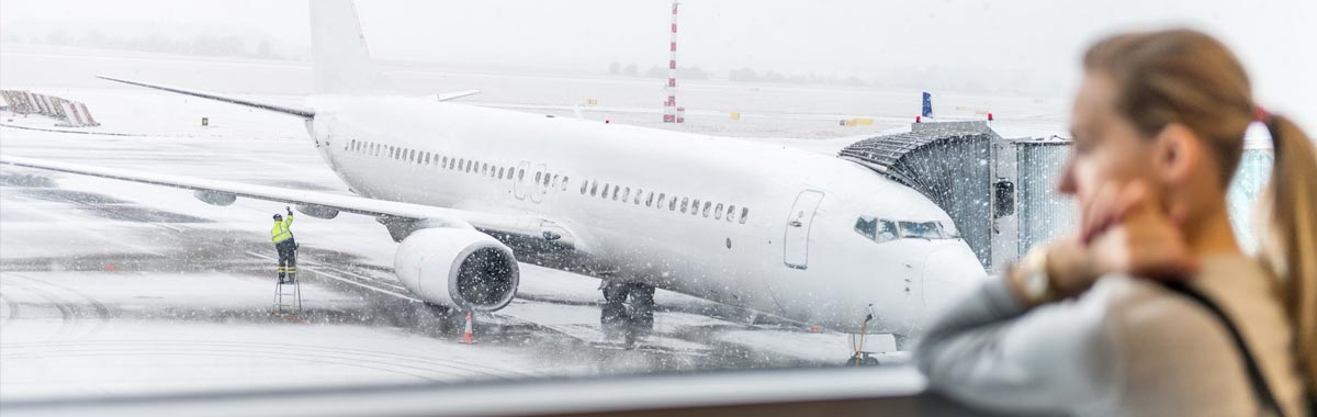 woman with canceled flight looks at plane stuck on runway in snow