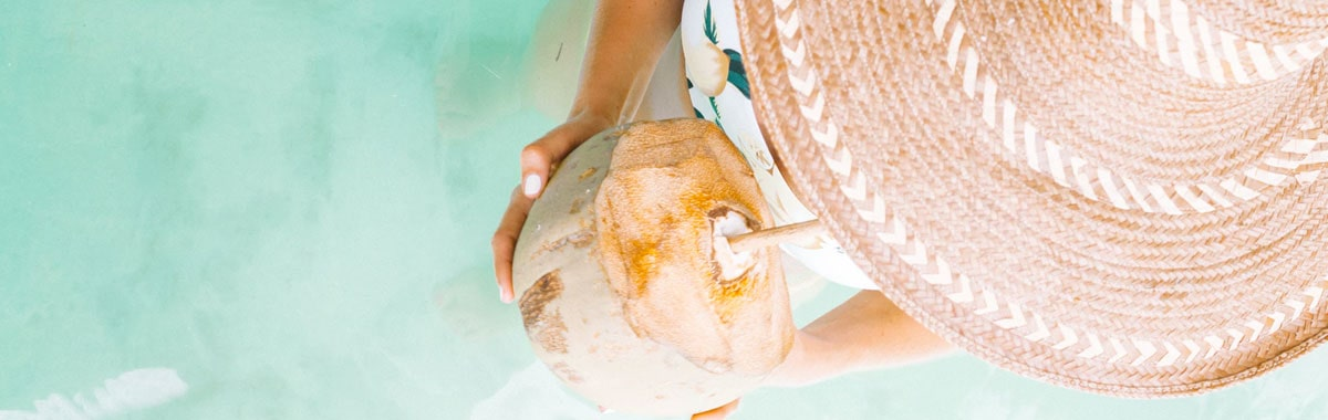 woman drinking from coconut in water on Caribbean vacation