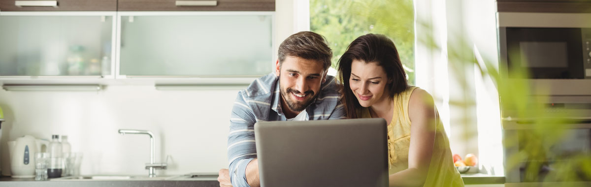 Man and woman on a computer viewing a travel insurance comparison