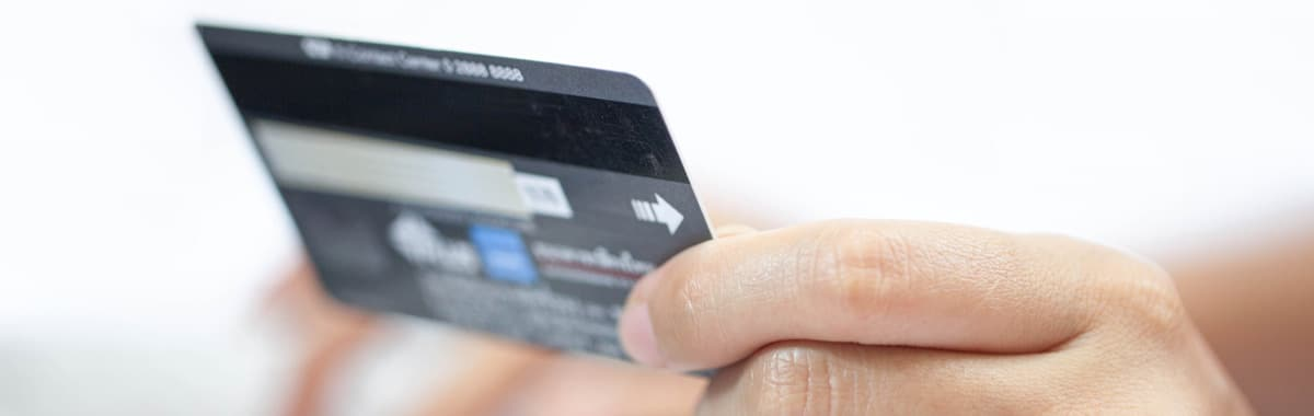 Person holding a credit card at a computer