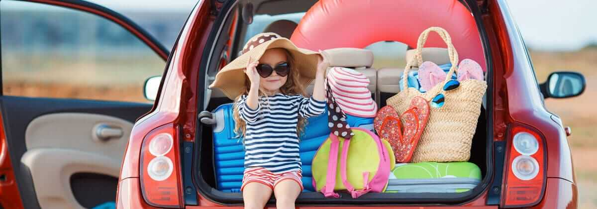 Girl sitting in trunk of car packed for a beach trip, ready to give some packing tips