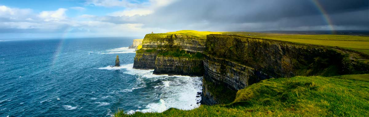 Scenic Irish vista with green grass, a rainbow, cliffs and ocean that makes you want to travel to Ireland