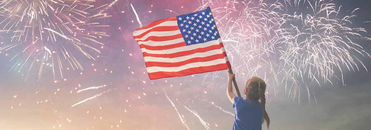 Girl holding American Flag with fireworks in background