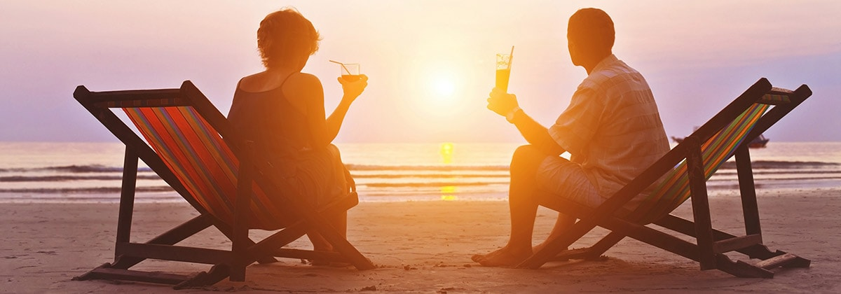 man and woman enjoying a relaxing vacation with drinks on the beach at sunset