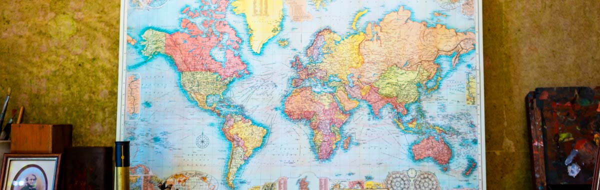 world map on wall showing most popular travel destinations for travel insurance